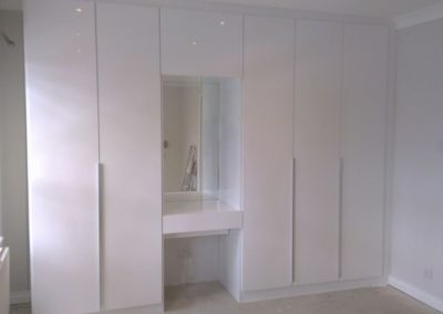 Great-example-of-Contemporary-White-Gloss-fitted-wardrobes-with-long-handles-1030x580